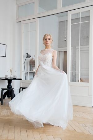 Blonde girl in a beautiful white wedding dress. A woman bride is waiting for the groom before the wedding Stockfoto