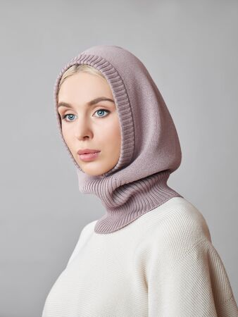 European Muslim woman with a blonde hair in a bonnet hood dressed on her head. Beautiful girl in sweater with soft skin, natural cosmetics Фото со стока