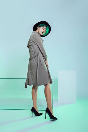 Woman in hat with creative green coloring hair and makeup, toxic strands of hair. Bright color curly hair on the girl head, professional makeup. Woman with tattoo in cloak Banque d'images