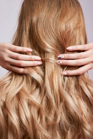 Beautiful strong hair of a woman, strengthening and restoring the hair roots. Beautiful manicure on the hands of a girl Stock Photo