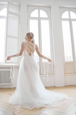 Beautiful slender blonde in the evening sun in a long white dress near a large window. Perfect hair and makeup for the bride, a new collection of wedding dresses Standard-Bild - 146851952