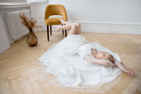 Romantic portrait of a woman on the floor in a beautiful long white dress. The girl is blonde with blue eyes and beautiful makeup on her face. Natural cosmetics