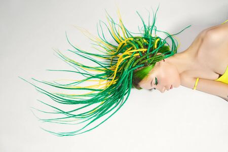 Portrait of a woman with creatively colored hair in green and yellow color. Colorful bright dreadlocks, beautiful modern makeup Stock Photo