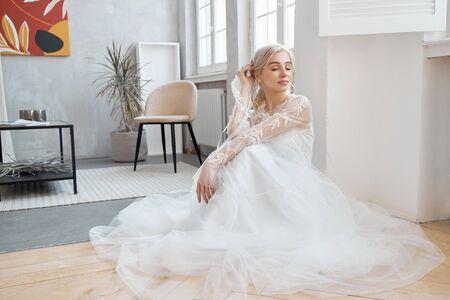 Mariée idéale assise sur le sol, portrait d'une jeune fille vêtue d'une longue robe blanche. De beaux cheveux et une peau propre et douce. Coiffure de mariage blonde
