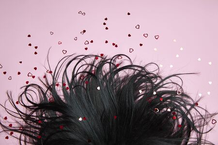 Black Hair on a pink background. Beautiful and strong hair, hair texture, root care