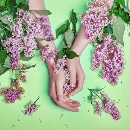 Fashion art hands natural cosmetics women, bright purple lilac flowers in hand with bright contrast makeup, hand care. Creative beauty photo of a girl sitting at table on contrasting green background
