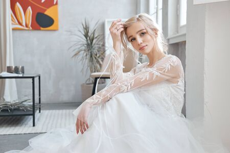 Ideal bride sitting on the floor, portrait of a girl in a long white dress. Beautiful hair and clean, soft skin. Wedding hairstyle blonde