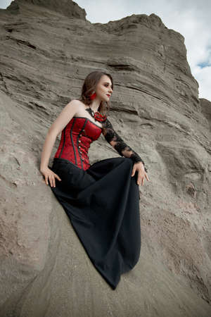 Beautiful anime woman in the sand. Red corset on the girl's body. Bright red makeup on the face Stock Photo