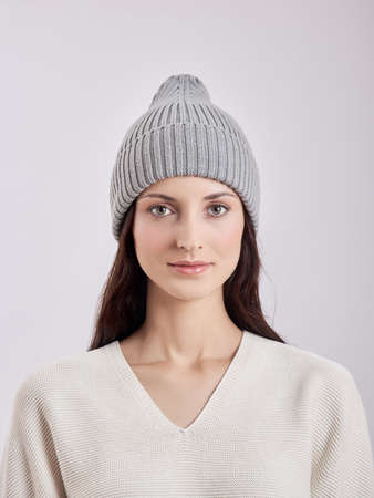 Beautiful woman in autumn hat on a white background. Autumn warm clothes