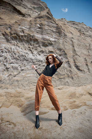 Fashion red-Haired girl in orange jeans posing in nature near sandy rocks, not like everyone else