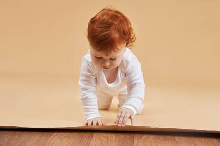 Little red-haired baby girl is playing on a beige background. Big mole on the forehead, not like everyone else