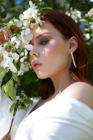 Beautiful girl in spring in the branches of flowering Apple bushes. Portrait of a woman on a bright summer day