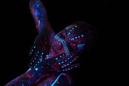 Art woman cosmos in ultraviolet light. Entire body is covered with colored droplets. Girl posing in the dark. Noise, out of focus