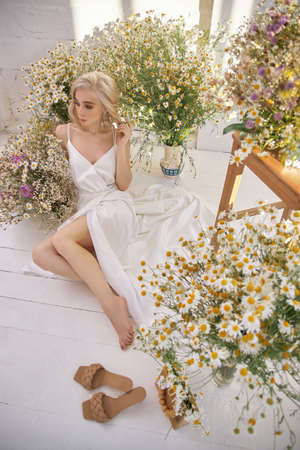Portrait of a sexy blonde in a beautiful white dress near a vase of wild flowers. Romantic girl with beautiful natural makeup