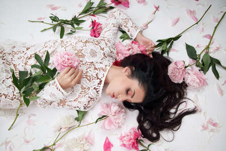 Beautiful nude brunette woman with peony flowers. Natural cosmetics and makeup, perfect skin