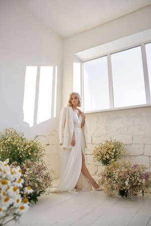 Sexy blonde woman in beautiful white dress stands near window in front of a bouquet of wild flowers. Romantic girl with beautiful natural makeup