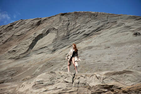 Fashion red-haired girl posing in nature near sandy rocks. Long curly hair and natural makeup