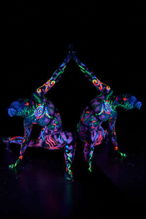 Art woman body art on the body dancing in ultraviolet light. Bright abstract drawings on the woman body neon color. Colored hair and face