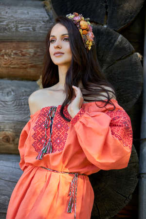 Beautiful Slavic woman in an orange ethnic dress and a wreath of flowers on her head. Beautiful natural makeup. Portrait of a Russian girl