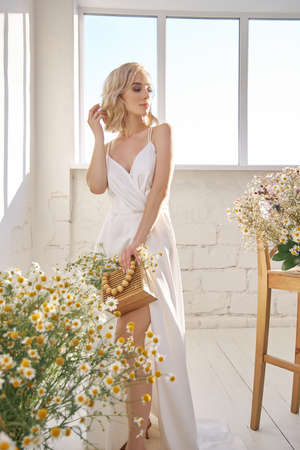 Blonde beauty woman in a white dress stands at the window in the evening sun. Portrait of a girl with a bouquet of wild flowers, natural makeup Zdjęcie Seryjne