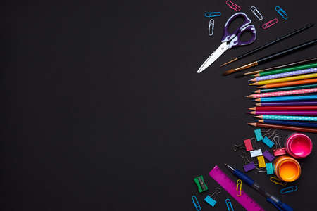 Colored school supplies for learning on a black background. Back to school. Pens, rulers, pencils and paper clips. Flat lay, top view, copy space
