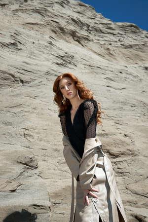 Beautiful woman with long red hair posing in nature. Beautiful natural makeup