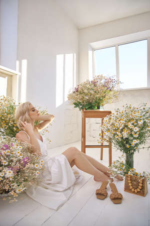 Beautiful blonde woman in a white dress is sitting on the floor among the chamomile flowers. Portrait of a girl with a bouquet of wild flowers Zdjęcie Seryjne