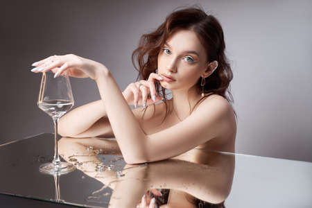 Woman holds a glass glass in her beauty hand. Rings and jewelry on table, luxurious life. Alcoholism