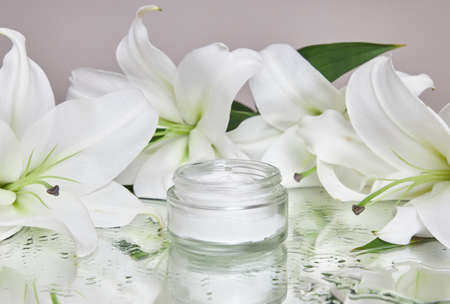 Beauty jar cream cosmetic with lily flowers lie on table, jar cream product on wet flower mirror moistening. Natural flower jar cream cosmetics for hand skin care. Smooth beauty skin