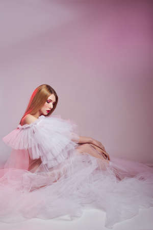 Beauty Woman bright red makeup sits on the floor. Art Girl in a transparent light dress on a pink background. Professional bright makeup woman Standard-Bild