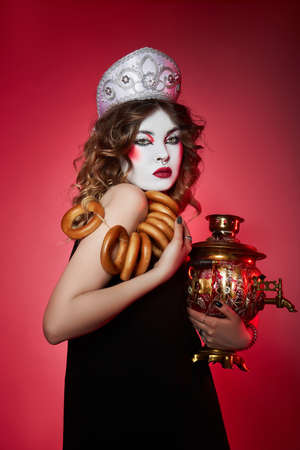 Fashion Russian woman in a kokoshnik with samovar on red background, bright makeup, make-up on woman face. Traditional Russian headdress, fashion modern style