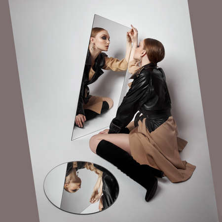 Beauty fashion young woman in trench coat, professional face makeup girl. Portrait of woman on white background reflected in mirror