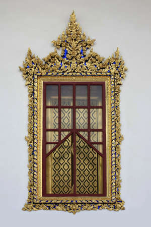 Ancient Golden carving wooden door of Thai temple in Bangkok, Thailand Stock Photo