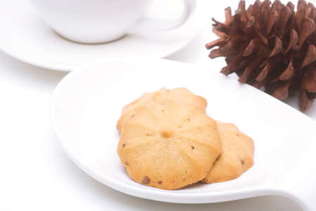 dry grass: cookies in cup and dry grass on a white background Stock Photo