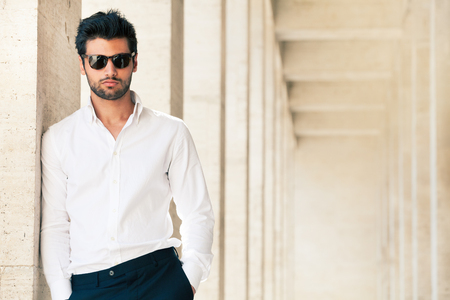 Charming and fashionable young man with sunglasses. Outdoors leaning against the marble wall. Stock fotó
