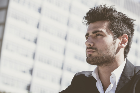 Close-up of handsome man with stylish haircut. Beard and intense look. Behind him the windows of a large building.