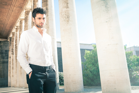 Handsome young elegant man outdoors. Nervous and pensive. A beautiful Italian man walking with his hands in his pockets near an ancient colonnade. His gaze is pensive and thoughtful.