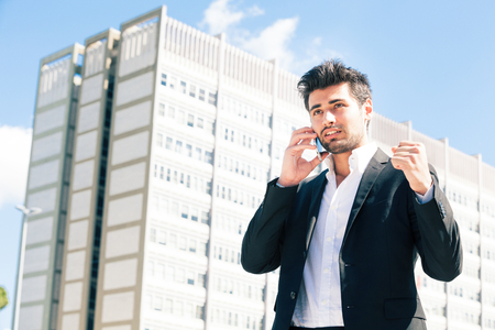 Career of young worker man. Business man. A young man talking on the phone. His hand closed in a fist. Behind him, an office building and blue sky.