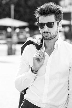 Handsome sexy man outdoors. Elegant and sensual. Sunglasses. elegance and beauty. Outdoor. Black and white. The young man wears a white shirt. Stock fotó