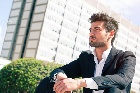 Handsome man model sitting watching. Career and job opportunities. Young entrepreneur, behind him a building with offices. Stock fotó