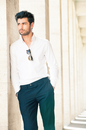 Handsome and stylish young man. Hair and beard fashionable. A beautiful young Italian man is outdoors. He is leaning against a marble wall. He wears a white shirt and dark trousers. Sunglasses.
