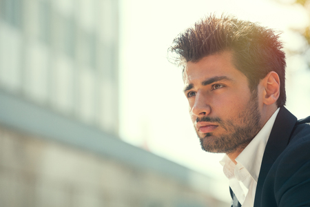 Young handsome man bearded and hairstyle. Hope attitude. He is outdoor with a strong day sunlight from behind.