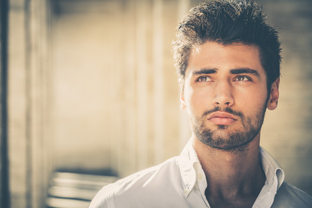 Handsome young man portrait. Intense look and eye-catching beauty. Fashionable hair and beard. The young man is wearing a white shirt. Stock fotó