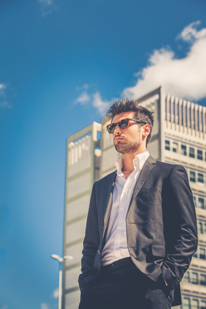 Handsome businessman with sunglasses, outdoor in the city. Charming and modern style, with shirt and suite. Cool hairstyle. Behind him at high-rise office building.