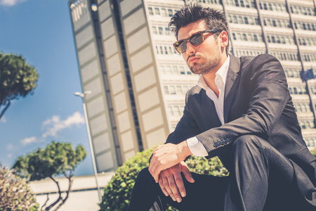 Handsome man model sitting with sunglasses. Career and job opportunities. Young entrepreneur, behind him a building with offices.