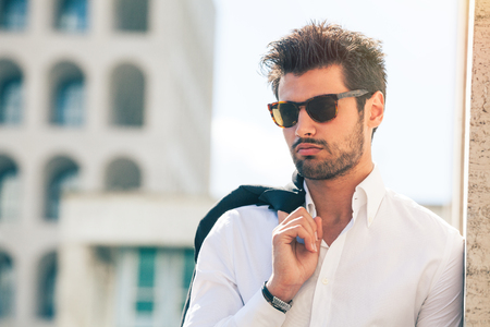 Charming and fashionable young man with sunglasses. Outdoors near a wall and buildings.
