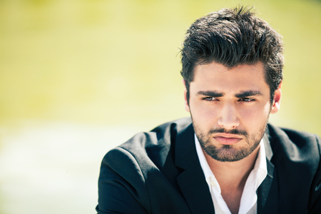 Concern and anxiety. Restless young man. A young handsome boy with dark hair. Outside, isolated on green background. With beard. Intense light. His attitude is thoughtful and concerned.