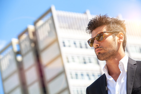 Handsome stylish man in the city. Wearing sunglasses. A beautiful and charming man with sunglasses outdoors. Intense light. White shirt and stylish jacket. Stock fotó