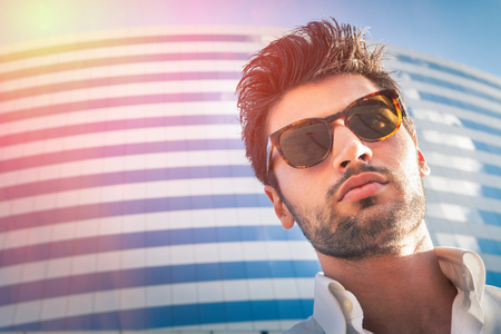Young modern man outdoor. Wearing sunglasses. Hairstyle and beard. Behind him at the large modern palace. Stock fotó