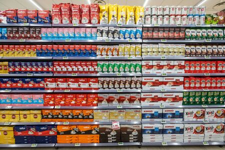 Rome / Italy. December 05, 2018: Shelving with products of different nature, variety of food displayed on the shelves inside a MA supermarket in Rome in Italy. Coffee packs.